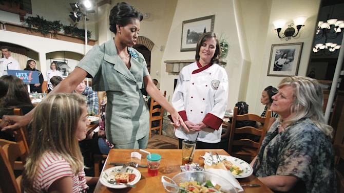 First Lady Michelle Obama, accompanied by Darden chef Julie Elkinton, second from right, talks to Charisse McElroy, right, and her daughter Jacqueline McElroy, 9, during a Let's Move! event in one of Darden's national restaurants in Hyattsville, Md., Thursday, Sept. 15, 2011. The first lady announced Darden Restaurants' commitment to reduce its calorie and sodium footprint and to provide greater choice and variety on its children's menus and make healthy options the default choice whenever possible. (AP Photo/Manuel Balce Ceneta)