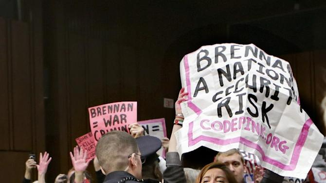 Protesters from CODEPINK, a social justice group opposed to U.S. funded wars, disrupt the start of a Senate Intelligence Committee's confirmation hearing for John Brennan, the top White House adviser on counterterrorism and nominee to lead the Central Intelligence Agency, Thursday, Feb. 7, 2013, on Capitol Hill in Washington. (AP Photo/J. Scott Applewhite)