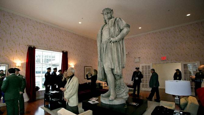 """Leaders of the Italian-American community, civil servants from New York, including police and sanitation workers and other guests, stand in what is known as the living room created by artist Tatzu Nishi that surrounds Gaetano Russo's 1892 sculpture of Christopher Columbus 75 Feet Above Columbus Circle Sunday, Oct. 7, 2012, in New York. The art  installation """"Tatzu Nishi: Discovering Columbus,"""" which brings people to eye level with the Columbus statue, became part of an annual wreath laying ceremony that celebrates Columbus Day. (AP Photo/Craig Ruttle)"""