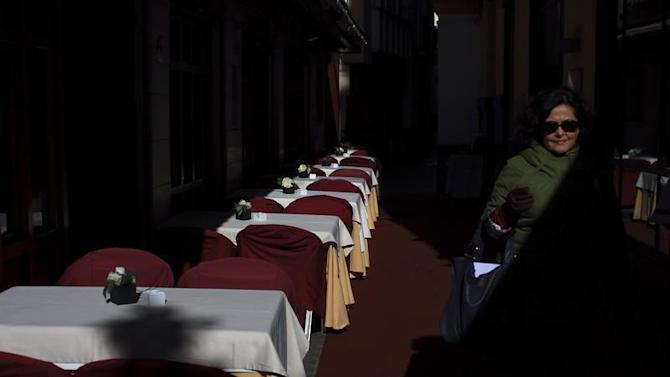 A woman walks past an empty restaurant in Seville