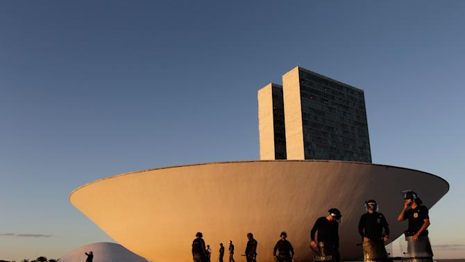 Police guard the building of Brazil's National Congress during a protest in Brasilia, Brazil, Thursday, June 20, 2013. President Dilma Rousseff called an emergency meeting of her top Cabinet members for Friday morning, more than a week after the protests began. Rousseff, who has a standoffish governing style, has been almost entirely absent from the public eye, making only one statement earlier in the week that peaceful protests are part of the democratic process. (AP Photo/Eraldo Peres)