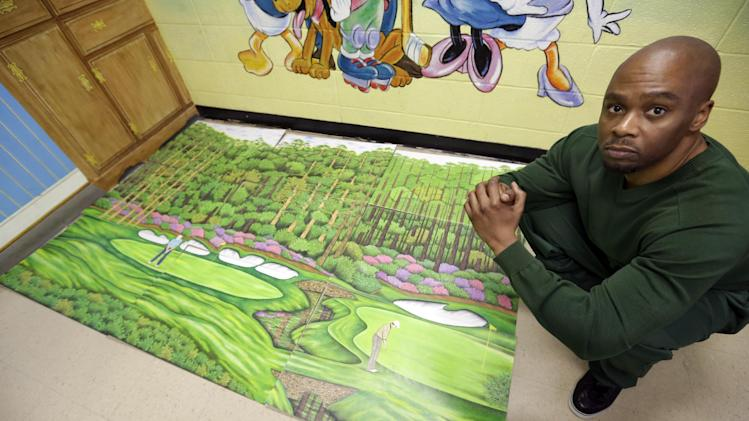 Attica Correctional Facility inmate Valentino Dixon poses with his golf art he creates in prison in Attica, N.Y., Thursday, May 16, 2013.   While serving a 39-year-to-life sentence for a murder he says he did not commit, Dixon draws, spending 10 to 12 hours a day illustrating a kind of serenity he has never known. (AP Photo/David Duprey)
