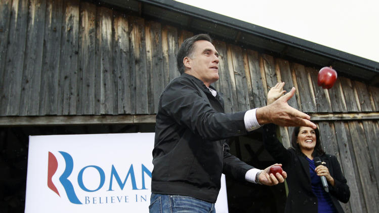 Republican presidential candidate, former Massachusetts Gov. Mitt Romney, accompanied by South Carolina Gov. Nikki Haley, throws an apple out to the audience as he campaigns at Harmon Tree Farm in Gilbert, S.C., Friday, Jan. 20, 2012. (AP Photo/Charles Dharapak)