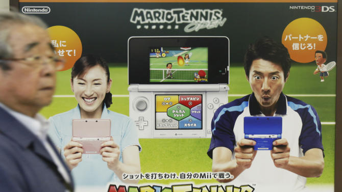 In this photo taken on June 7, 2012, a man walks by an advertisement poster of a Nintendo 3DS game software in Tokyo. Nintendo Co. trimmed its red ink for the fiscal first half to a 28 billion yen ($350 million) loss, but the Japanese game maker lowered its sales and profit forecasts Wednesday, Oct. 24 for the full year ahead of the launch of its new Wii U home console. (AP Photo/Koji Sasahara)