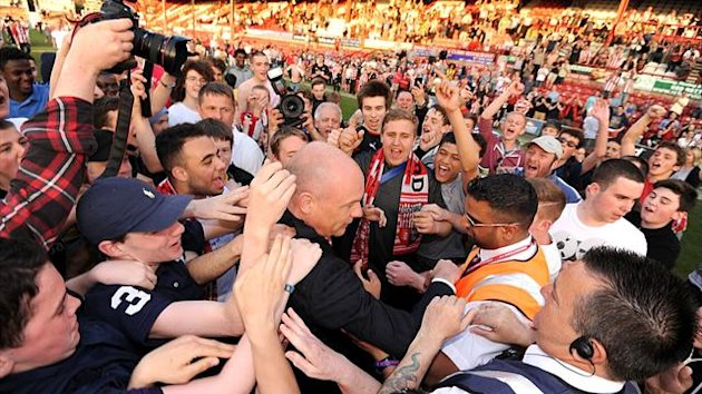 Brentford manager Uwe Rosler is mobbed by home fans on the pitch after the final whistle (PA)