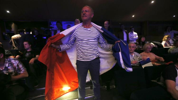 A France's far-right National Front political party supporter draped in a French flag attends a rally for local elections in Marseille