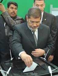 Egyptian President Mohamed Morsi casts his vote at a polling station near the presidential palace in Cairo on December 15, 2012. Egypt&#39;s opposition has called for mass protests after Islamists backing President Mohamed Morsi claimed victory in the first round of a referendum it alleges was riddled with polling violations