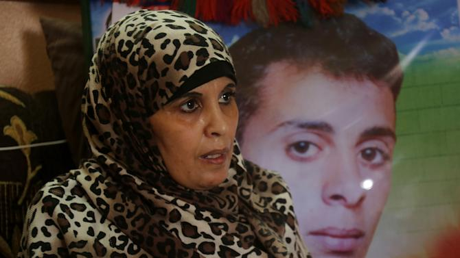 In this June 3, 2014 photo, Rawda Zanoun, 48, speaks during an interview with The Associated Press in front of a portrait of her son, Alaa Eldin, who was killed in a 2007 fight between Hamas and Fatah days before the Hamas take over in Gaza City. Foes Hamas and Fatah managed to set aside some of their differences to form a Palestinian unity government, but the hardest part of reconciliation may still lie ahead. (AP Photo/Hatem Moussa)