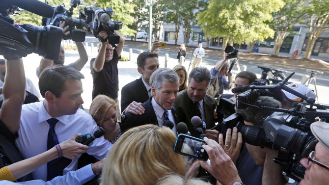 Former Virginia Gov. Bob McDonnell, center, is swarmed by media as arrives at Federal Court with his daughter Cailin Young, left of McDonnell, in Richmond, Va., Monday, Aug. 25, 2014. Prosecutors are expected to cross-examine the former governor during his corruption trial Monday. (AP Photo/Steve Helber)