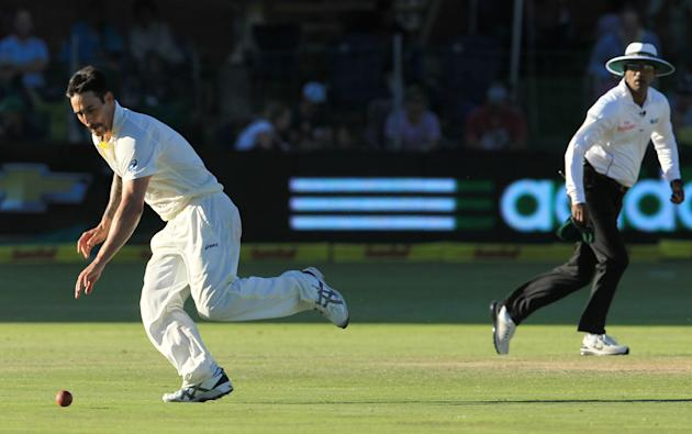 Australia's bowler Mitchell Johnson, left, runs as he attempts a fielding off own bowling whilst umpire Kumar Dharmasena of Sri Lanka, right, watches on the third day of their 2nd cricket test mat