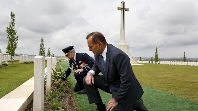 Australian Prime Minister Tony Abbott and Defence Force Air Chief Marshal Mark Binskin place crosses at the foot of headstones at the Australian National Memorial in Villers-Bretonneux