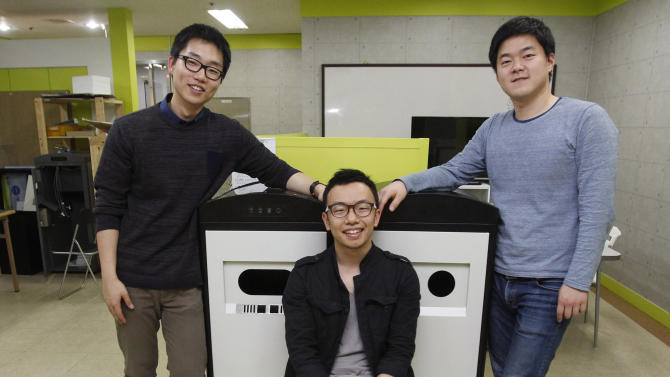 """In this Tuesday, May 14, 2013 photo, from left, Ecube Labs CEO Kwon Sunbeom, his co-founders Lee Seungjae and Kwon Hyungsuk pose with their product, a solar energy-powered garbage bin, at their office in Seoul, South Korea. Instead while his peers were seeking jobs at Samsung and LG, Kwon Sunbeom scaled back his studies and started the company with friends. Together they invented the garbage bin that compresses rubbish using solar power and wirelessly communicates to be collected when full. Using 50 million won ($44,000) of their own money and channeling the business in a garage spirit that made Silicon Valley famous, they lived for a month in a shabby factory without air conditioning, subsisting on instant noodles, to make their first prototype. So far they have sold 31 of their """"Smart Bins"""" to universities in Seoul and another 12 to Saudi Arabia and the United Arab Emirates. (AP Photo/Ahn Young-joon)"""