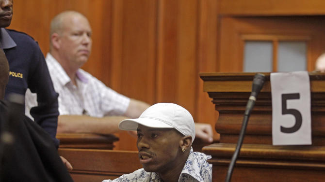 Xolile Mngeni, centre,  accused of the slaying of Anni Dewani, sits in the dock, in a courtroom, in Cape Town, South Africa, Monday, Nov. 19, 2012, as he awaits the court's verdict. Mngeni,was arrested for the killing of 28-year-old Anni Dewani. Prosecutors say Mngeni was hired by Dewani's British husband to carry out the November 2010 killing, which was made to look like a car hijacking. (AP Photo/Schalk van Zuydam)
