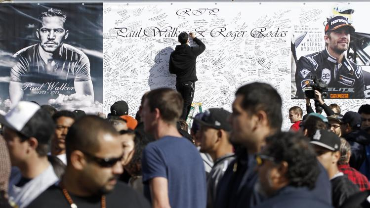 "A man signs a large condolence card during an unofficial memorial event for ""Fast & Furious"" star Walker in Santa Clarita"
