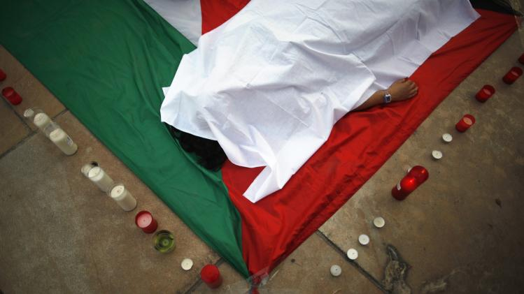 A woman lies on a Palestinian flag during a protest against Israel's military action in the Gaza Strip, in Malaga