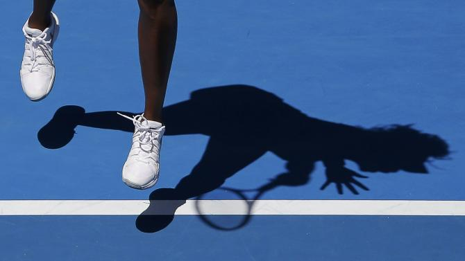Venus of the U.S. casts a shadow as she serves to compatriot Keys during their women's singles quarter-final match at the Australian Open 2015 tennis tournament in Melbourne