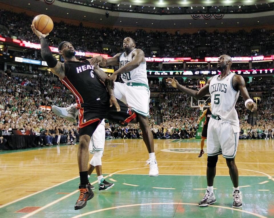 Miami Heat forward LeBron James (6) shoots past Boston Celtics power forward Brandon Bass (30) and forward Kevin Garnett (5) on a drive to the basket during the first half of Game 4 in their NBA basketball Eastern Conference finals playoffs series in Boston, Sunday, June 3, 2012. (AP Photo/Charles Krupa)