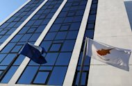 <p>A Cypriot and European Union (EU) flag fly in Nicosia on June 5. The International Monetary Fund said Wednesday that Cyprus has asked for financial aid amid the eurozone sovereign debt crisis.</p>