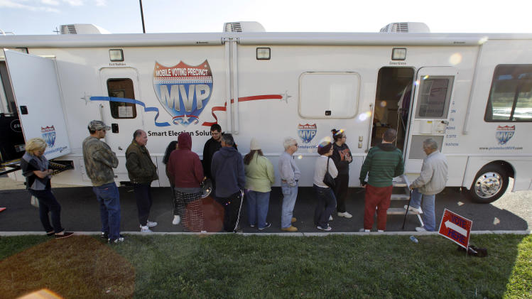 People, many displaced by Superstorm Sandy, line up to vote  Monday, Nov. 5, 2012, in Burlington, N.J., at a Mobile Voting Precinct. Many victims displaced by Superstorm Sandy are taking advantage of offers to vote early. (AP Photo/Mel Evans)