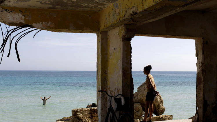 In this May 23, 2013 file photo, a woman stands in what remains of a destroyed school as she watches a fisherman on the shores of Havana, Cuba. With its coastal towns and cities, the Caribbean is one of the most vulnerable regions to a changing climate. (AP Photo/Franklin Reyes)