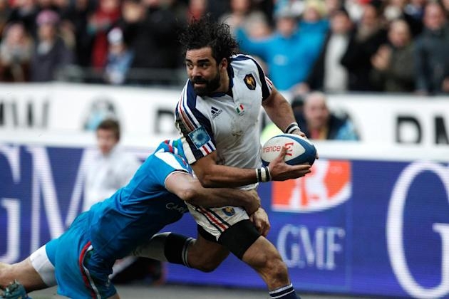France's Yoann Huget, right, is tackled by Italy's Leonardo Sarto, during their Six Nations rugby union international match, at the Stade de France, in Saint Denis, outside Paris, Sunday, Feb