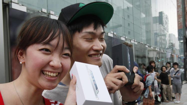 Kae Shibata 20, left, and Yutaro Noji, 21, show off Apple's iPhone 5 after they bought at a store in Tokyo Friday morning, Sept. 21, 2012. (AP Photo/Koji Sasahara)