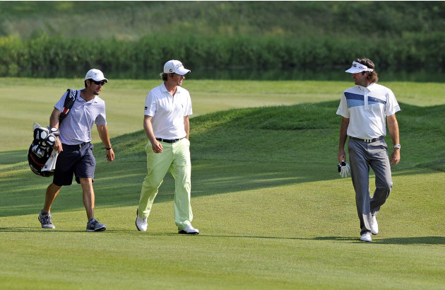 Master champion Bubba Watson, right, and U.S. Open Champion Webb Simpson, center, share a moment on the 15th fairway at the Travelers Championship golf tournament in Cromwell, Conn., Thursday, June 21