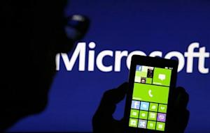 Photo illustration shows a man silhouetted against a video screen with the Microsoft logo in the background as he poses with a Nokia Lumia 820 smartphone in Zenica