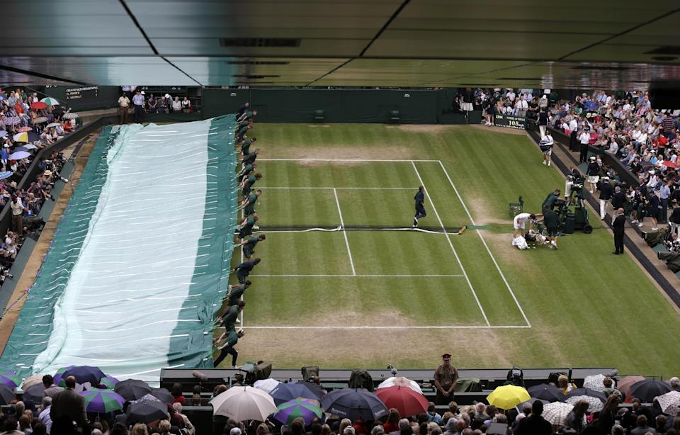 Ground staff pull a rain cover over Centre Court as rain delays play between Andy Murray of Britain and David Ferrer of Spain during a quarterfinals match at the All England Lawn Tennis Championships at Wimbledon, England, Wednesday, July 4, 2012. (AP Photo/Alastair Grant)