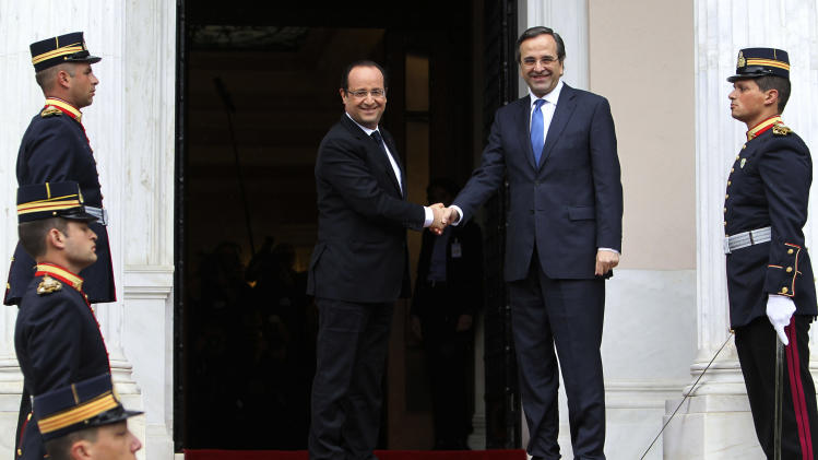 Greece's Prime Minister Antonis Samaras, center right, welcomes French President Francois Hollande at Maximos mansion in Athens, Tuesday, Feb. 19, 2013. Hollande arrived in Athens Tuesday for a brief visit of little more than six hours, with talks to focus on Greece's deep financial crisis. (AP Photo/Thanassis Stavrakis)