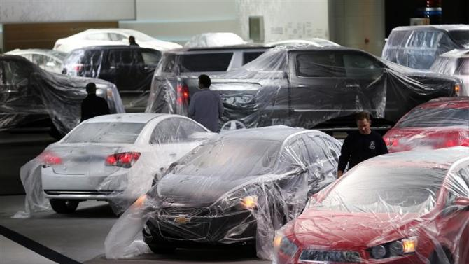 Vehicles are covered with protective wrap as workers prepare the General Motors automakers display ahead of the media preview of the North American International Auto Show in Detroit