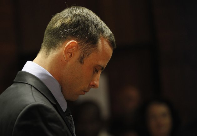Oscar Pistorius stands in the dock during a break in court proceedings at the Pretoria Magistrates court