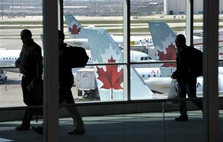 Passengers walk past Air Canada planes on the runway at Pearson International Airport in Toronto