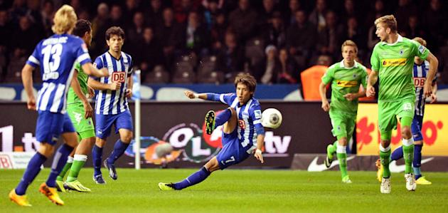 Berlin's Hajime Hosogai, center, shoots the ball during the German first division Bundesliga soccer match between Hertha BSC Berlin and Borussia Moenchengladbach, in Berlin, Germany, Saturday, Oct. 19