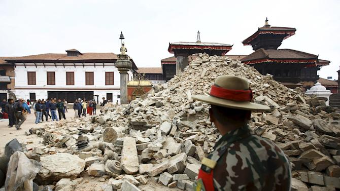 Nepalese army personnel stands in front of a collapsed temple a day after an earthquake in Bhaktapur