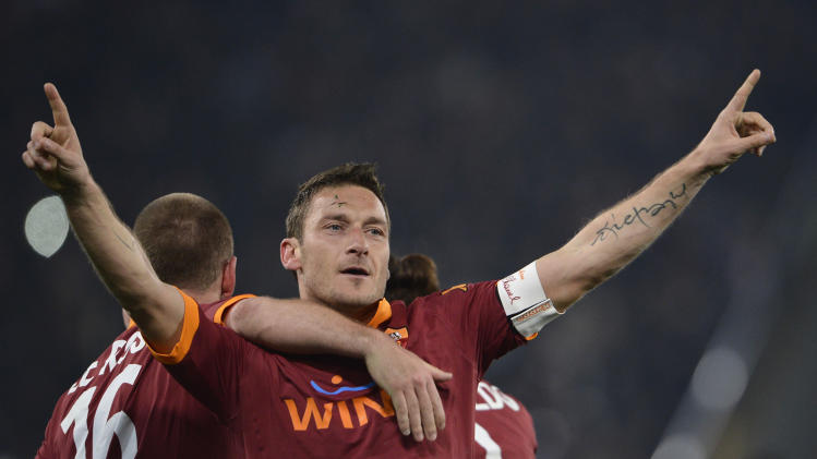 AS Roma's Francesco Totti, center, hugged by teammate Daniele De Rossi, celebrates after scoring during a Serie A soccer match between AS Roma and Juventus at Rome's Olympic stadium, Saturday, Feb. 16, 2013. (AP Photo/Alfredo Falcone, LaPresse)