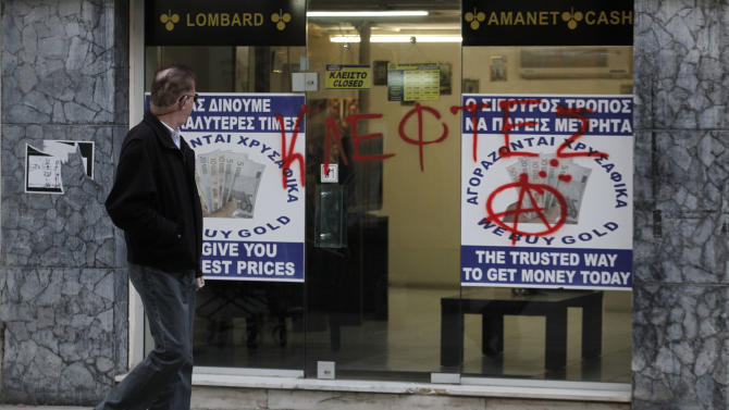 "A man passes a sprayed entrance of a store that buys gold which reads in Greek "" thieves"" in capital Nicosia, Cyprus, Monday, March 25, 2013.  Cyprus secured what its politicians described as a ""painful"" solution to avert imminent bankruptcy, agreeing early Monday to slash its oversize banking sector and make large account holders take losses to help pay to secure a last-minute euro10 billion (US$13 billion) bailout. (AP Photo/Petros Giannakouris)"