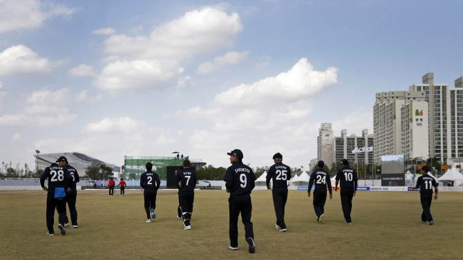 South Korea's cricket team make their way onto the field for their men's Twenty20 quarter-final cricket match against Sri Lanka at the 17th Asian Games in Incheon