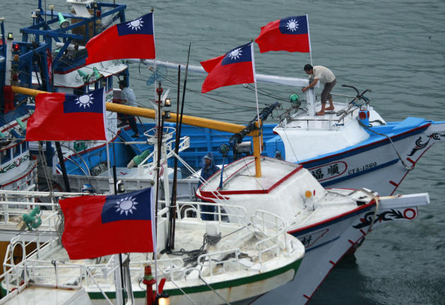 A fisherman raises a Taiwanese national flag as several dozen fishing boats set out from the Suao harbor, northeastern Taiwan, to the disputed islands in the East China Sea, Monday, Sept. 24, 2012. Th