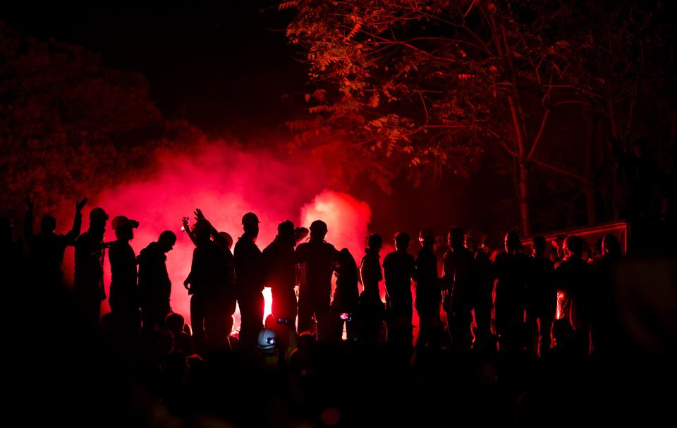 FILE - In this Wednesday, June 12, 2013. file photo, protesters chant anti-government slogans, silhouetted by the light of flares in Taksim square, in Istanbul, Turkey. (AP Photo/Vadim Ghirda, File)