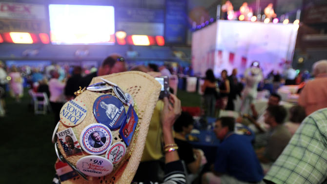 Judy Griffin, of Georgia, takes photos while wearing a hat with Republican Party buttons during the 2012 Tampa Bay Host Committee's welcoming event for the delegates of the Republican National Convention on Sunday, Aug. 26, 2012 at Tropicana Field in St. Petersburg, Fla. (AP Photo/The Tampa Tribune, Chris Urso, Pool)
