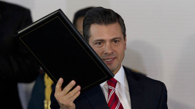 Mexico's President Enrique Pena Nieto holds up a folder containing documents describing an education reform proposal during an event to announce it in Mexico City, Monday, Dec. 10, 2012. Pena Nieto is proposing sweeping reforms to the public education system widely seen as moribund, taking on Elba Esther Gordillo, an iron-fisted union leader who is considered the country's most powerful woman and the main obstacle to change. (AP Photo/Alexandre Meneghini)