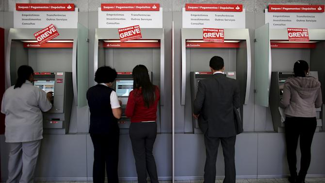 """Posters read """"We are on Strike"""" are displayed as citizens withdraw money at automatic teller machines (ATM) at a bank in Sao Paulo"""