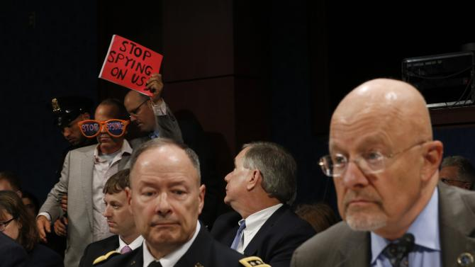 U.S. Director of National Intelligence James Clapper and General Keith Alexander, director of National Security Agency, testify at House Intelligence Committee hearing as a protester against spying is removed from the hearing on Capitol Hill in Washington