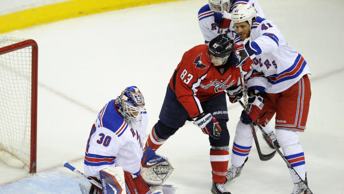 New York Rangers goalie Henrik Lundqvist (30), of Sweden, and Stu Bickel (41) battle for the puck against Washington Capitals center Jay Beagle (83) during the first period of Game 4 of an NHL hockey Stanley Cup second-round playoff series, Saturday, May 5, 2012, in Washington. (AP Photo/Nick Wass)