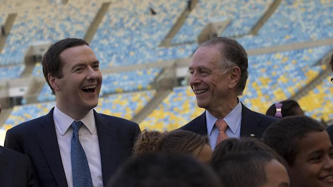 Britain's Chancellor of the Exchequer George Osborne, left, and President of Brazil's Olympic Committee Carlos Arthur Nuzman smile as they pose for a photo during a visit to the Maracana stadium in Rio de Janeiro, Brazil, Monday, April 7, 2014. The city of Rio de Janeiro will host the Olympics in 2016. (AP Photo/Silvia Izquierdo)