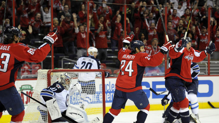 Washington Capitals center Matt Hendricks, right, celebrates his goal with Jay Beagle (83) and Aaron Volpatti (24) as Winnipeg Jets goalie Ondrej Pavelec (31), of the Czech Republic, looks on during the first period of an NHL hockey game, Tuesday, April 23, 2013, in Washington. (AP Photo/Nick Wass)