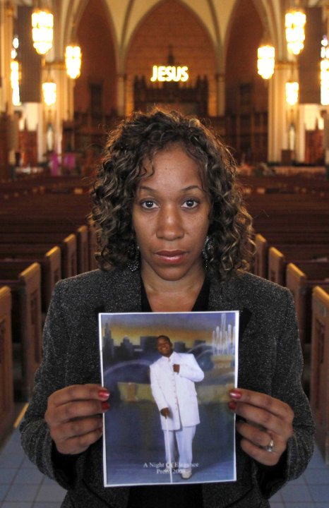 In this March 9, 2011 photo, Pam Bosley stands inside the Chicago's St. Sabina Catholic Church and poses with a photograph of her son, Terrell, who was gunned down in 2006. Bosley now works with kids 