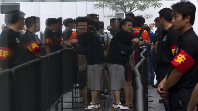 Security workers guard an entrance while customers who ordered the new iPad online wait in a line to enter an Apple store in Beijing, China, Friday, July 20, 2012. The latest iPad has received an uneventful launch in China after Apple Inc. settled a lawsuit with a local company over ownership of the popular tablet computer's name. (AP Photo/Alexander F. Yuan)