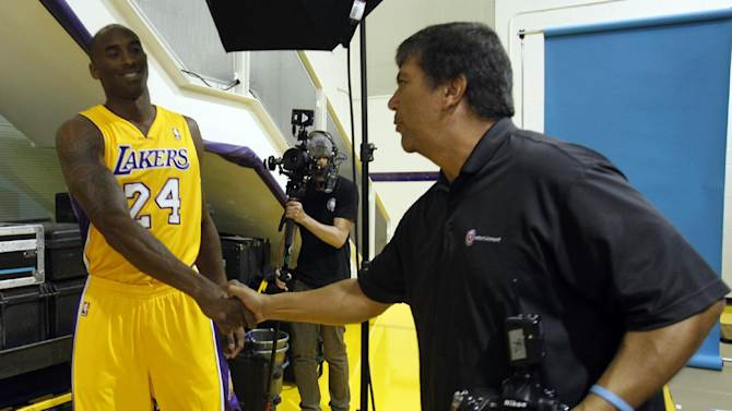 Los Angeles Lakers guard Kobe Bryant, left, shakes hands with NBA photographer Juan Ocampo during their NBA basketball media day at the team's headquarters on Saturday, Sept. 28, 2013, in El Segundo, Calif